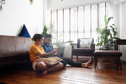 young couple sitting on the floor looking at a laptop